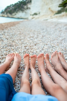 Closeup of the feet of family on the white sandy beach