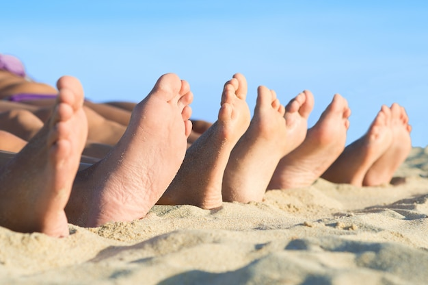 Closeup of feet row lying in line at summer beach