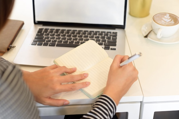 Closeup female accountant taking notes on notebook with opened laptop on desk