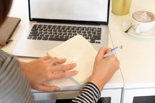책상에 열린 노트북이 있는 노트북에 메모를 하는 근접 촬영 여성 회계사
