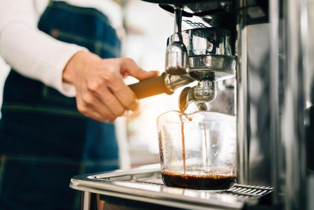 クローズアップの女性バリスタの手がビーカーの中に熱いブラックコーヒーを注ぐのを待っているコーヒーマシンに金属フィルターを挿入します