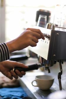 クローズアップ女性バリスタがコーヒーショップでコーヒーマシンで飲み物の注文を準備してコーヒーを作る