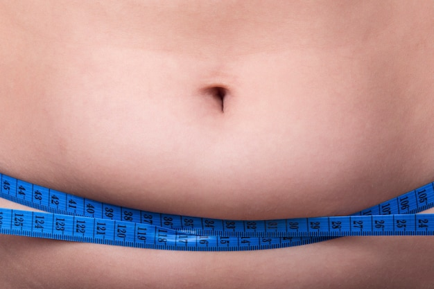 Closeup female belly with overweight wrapped with a measuring tape, the concept of proper nutrition and diet for weight loss
