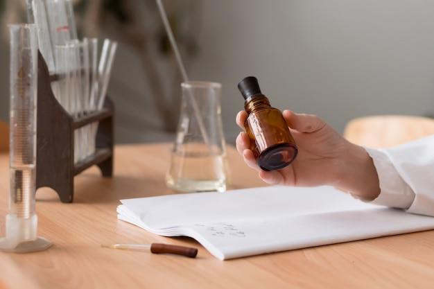 Женщина-химик крупным планом держит в руке бутылку с йодом и делает заметки в лаборатории