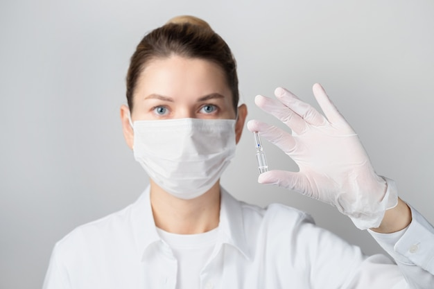 Closeup of a female doctor or scientist in a protective mask with an ampoule in her hand