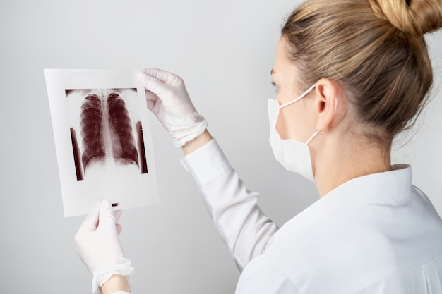 Closeup of a female doctor or scientist in a protective mask with a shot of the lungs
