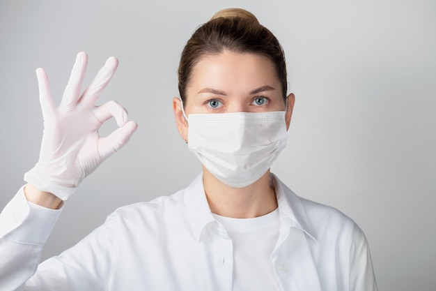 Closeup of a female doctor or scientist wearing a protective face mask on a gray background