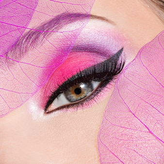 Closeup female eye with  beautiful fashion bright pink makeup