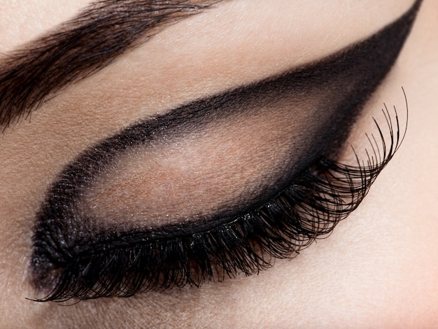 Closeup female eye with creative fashion make-up. brown eyeshadow