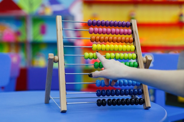 Closeup of female hand calculating  on wooden abacus for number calculation.