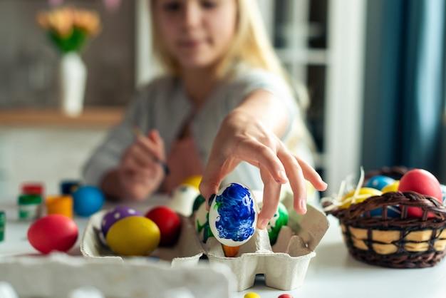 근접 촬영 여성 손에 파란색 계란을 보유하고있다. 계란에 중점을 둡니다. 부활절 준비