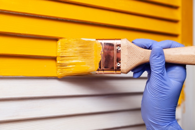 Рука крупного плана женская в фиолетовой резиновой перчатке при paintbrush крася естественную деревянную дверь с оранжевой краской. цветной яркий креативный дизайн интерьера. как покрасить деревянную поверхность. выбранный фокус