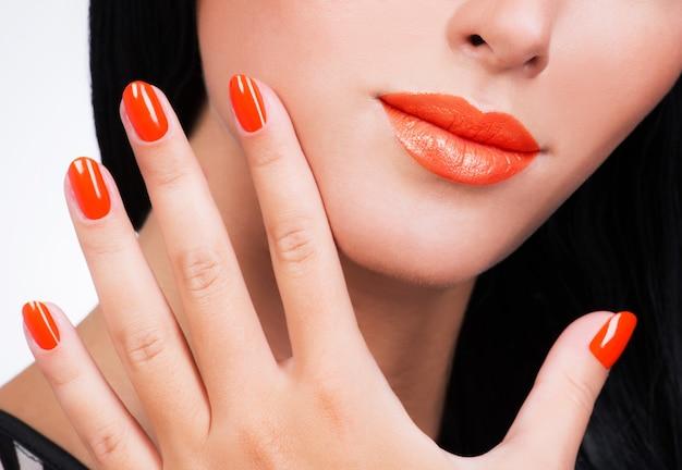 女性の顔に美しいオレンジ色の爪でクローズアップ女性の手