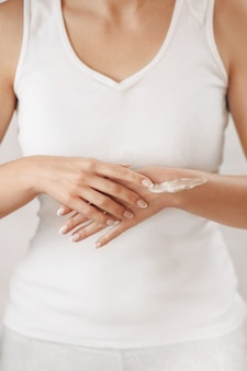 Closeup of female hands applying hand cream.hand skin care. girl hands with french manicure.
