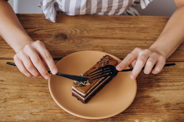 クローズアップの女性の手は茶色のプレートにチョコレートデザートをカット菓子やレストランのメニュー