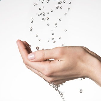 Closeup female hands under the falling drops of  water - skin care concept