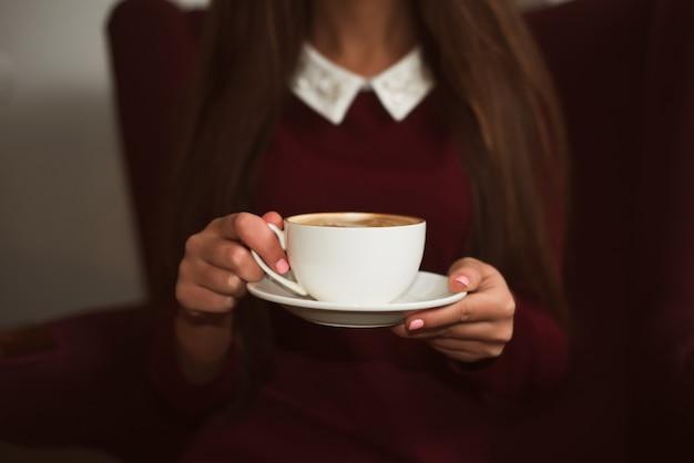 受け皿にコーヒーのカップを保持している女性の手のクローズアップ。