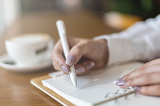 Closeup female hands making paper notes in notepad use pen table cafeteria writing diary planning