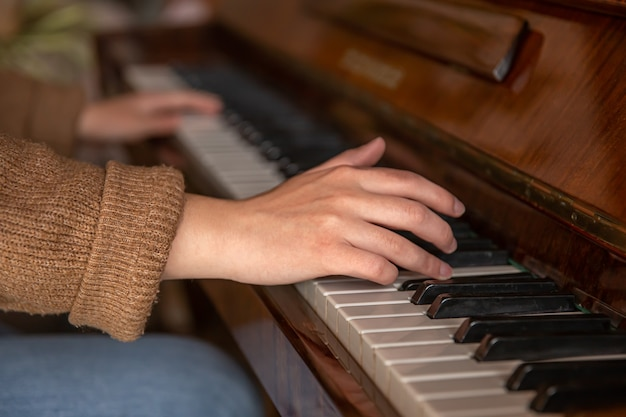Closeup of female hands playing the piano