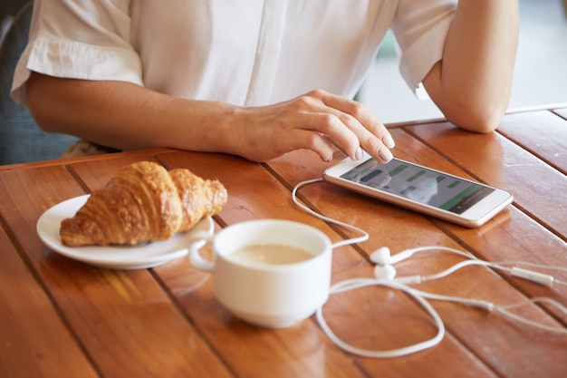 Closeup of female hands texting a message on the smartphone while having morning coffee