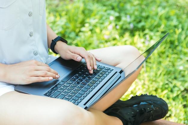 Крупным планом женские руки работают или учатся онлайн на ноутбуке в парке и наслаждаясь время в одиночестве в природе