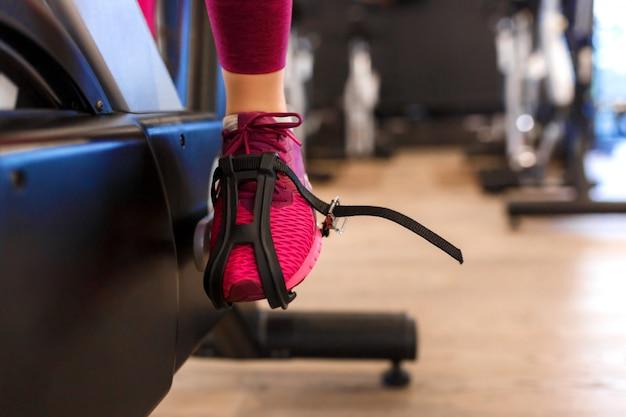 Closeup female leg in pedal of exercise bike