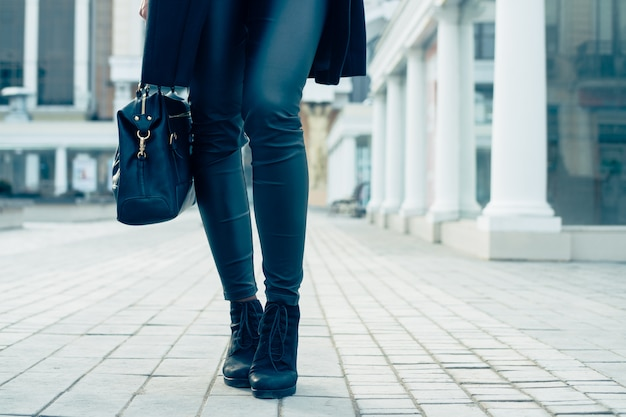 Closeup of female legs in black pants and boots
