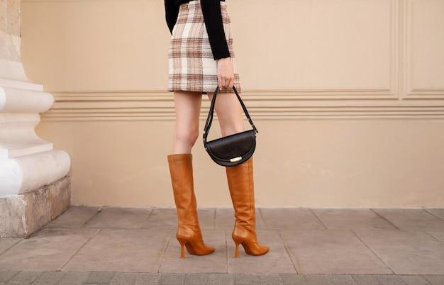 Крупным планом женские ножки в красных сапогах на высоких каблуках с черной сумочкой. модный уличный осенний наряд