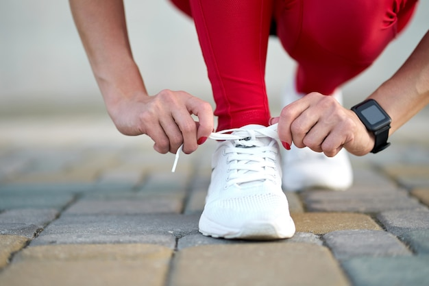 Closeup of female legs in stylish red sport leggings and trendy white sneakers. active slim woman on a training. get ready for start.