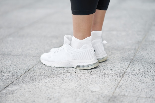 Closeup of female legs in stylish white sneakers. active woman on a training. ready to start.