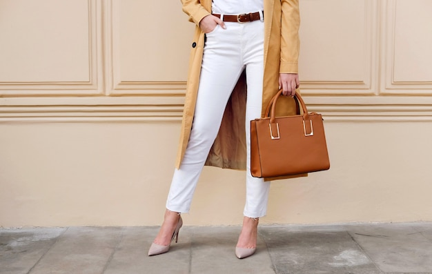 クローズアップの女性の足。茶色のハンドバッグとコートと白いジーンズの女性。ファッションストリート秋の服