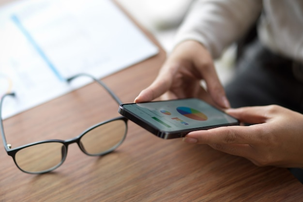 Closeup of female looking on financial chart on her smartphone with eyeglasses and financial report