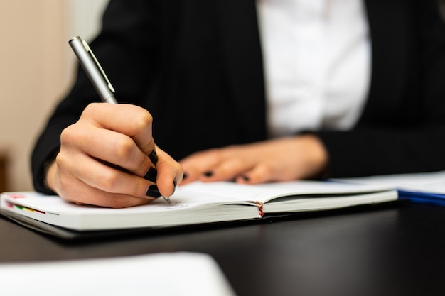 Closeup of a female manager writing and taking notes on a sheet in her office