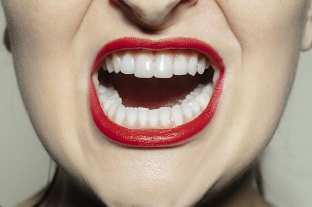 Крупным планом женский рот с ярко-красными блеском губ