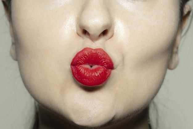 真っ赤な光沢のある唇とクローズアップの女性の口