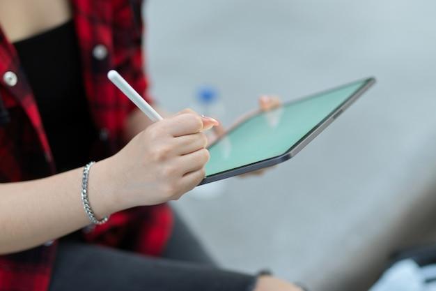 Крупным планом женские руки с помощью портативного планшета со стилусом, сидя в парке, размытый фон