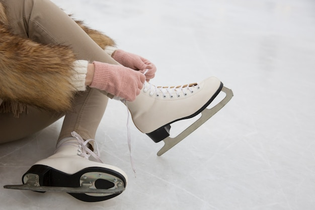 Closeup of female sitting on ice rink and tying shoelaces