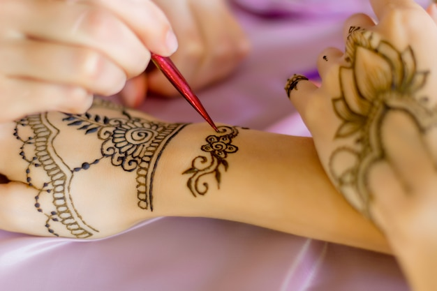 Closeup female slender wrists painted with traditional oriental mehndi ornaments. process of painting womens hands with henna, preparing for indian wedding. light pink fabric on background.