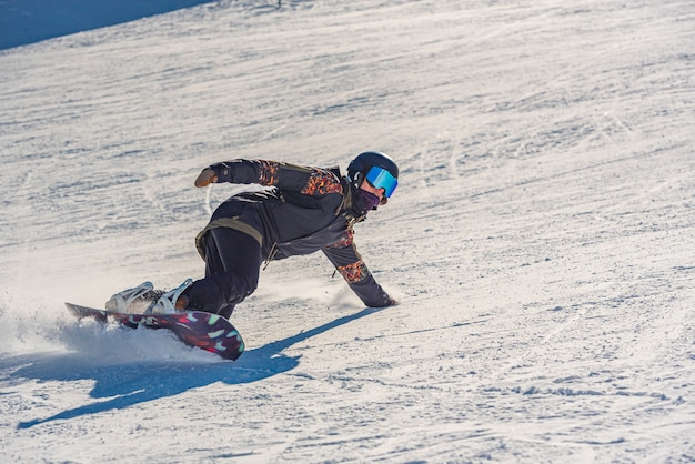 Closeup of a female snowboarder in motion on a snowboard in a mountain