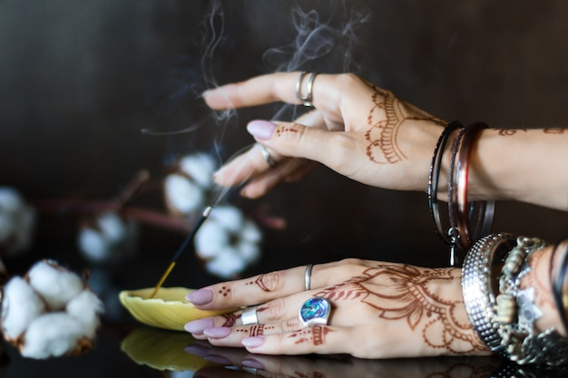 Closeup of female wrists painted with henna traditional indian oriental mehndi ornaments. hands dressed in bracelets and rings put aromatic stick in stand.  branch with cotton flowers on background.