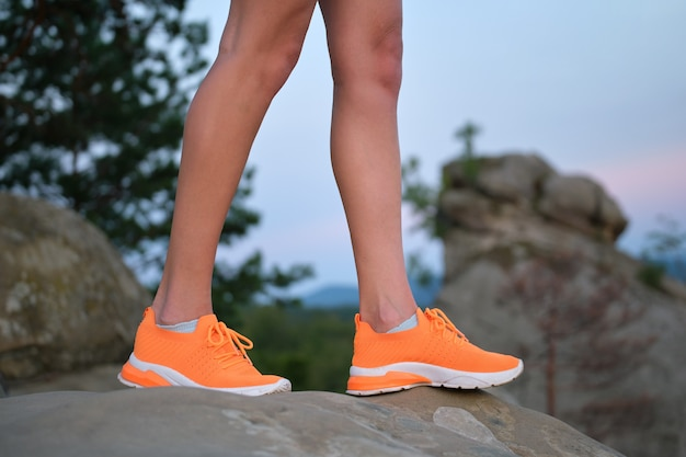Closeup of female young slim legs in bright orange sneaker shoes standing on mountain hiking trail in summer evening. active lifestyle, jogging in nature and exercise on fresh air concept.