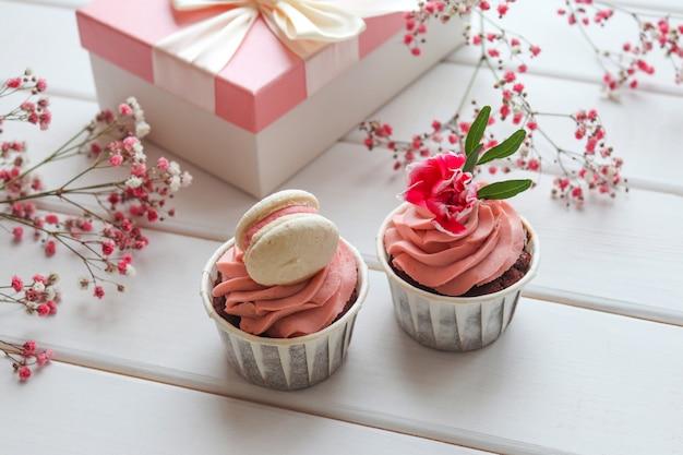 カップケーキギフトボックスとピンクの花のクローズアップお祝いの構成休日の誕生日パーティー