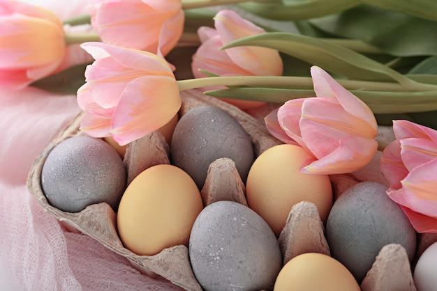 黄色と青のパステルカラーの自然な卵、白い背景のチューリップのクローズアップお祝いイースター構成