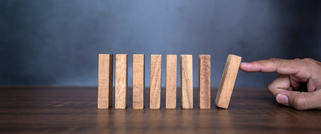 Closeup fingers prevent the wooden block building collapse game stick from falling domino