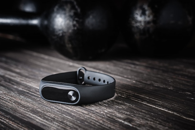 Closeup fitness tracker and old dumbbells on dark background