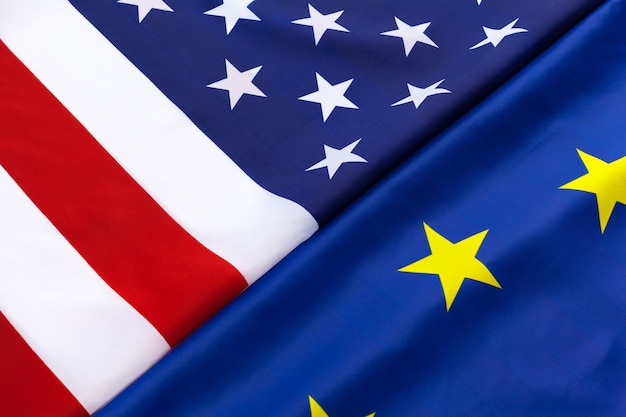 Closeup of flags of usa and european union lying together on table