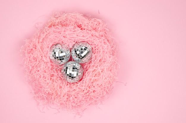 Крупным планом плоская форма гнезда розового бумажного наполнителя с серебряными стеклянными елочными шарами на розовом фоне