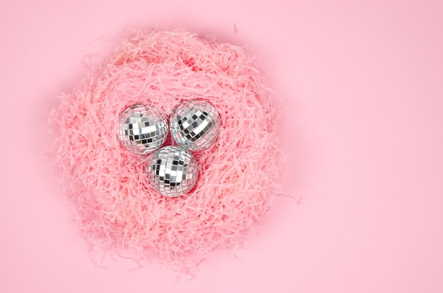 Closeup flat lay pink paper filler nest shape with silver glass christmas balls on a pink background