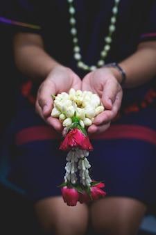 Closeup flower garlands on the hands of women