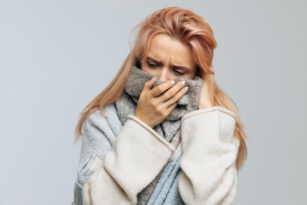 Женщина, завернутая в теплый шарф, смотрит вниз, closeup.flu сезона